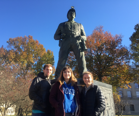 three team members posing in front of a statue of a coal miner