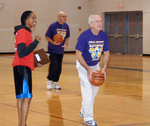 A participant of the Mid-Carolina Senior Games attempts to hit a 3-point shot at the Pope Fitness Center, by Tech. Sgt.