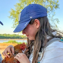 Melissa Marchese taking feather samples with boat driver and field assistant, Pancho.