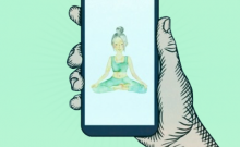 Hand holding phone with image of person meditating.